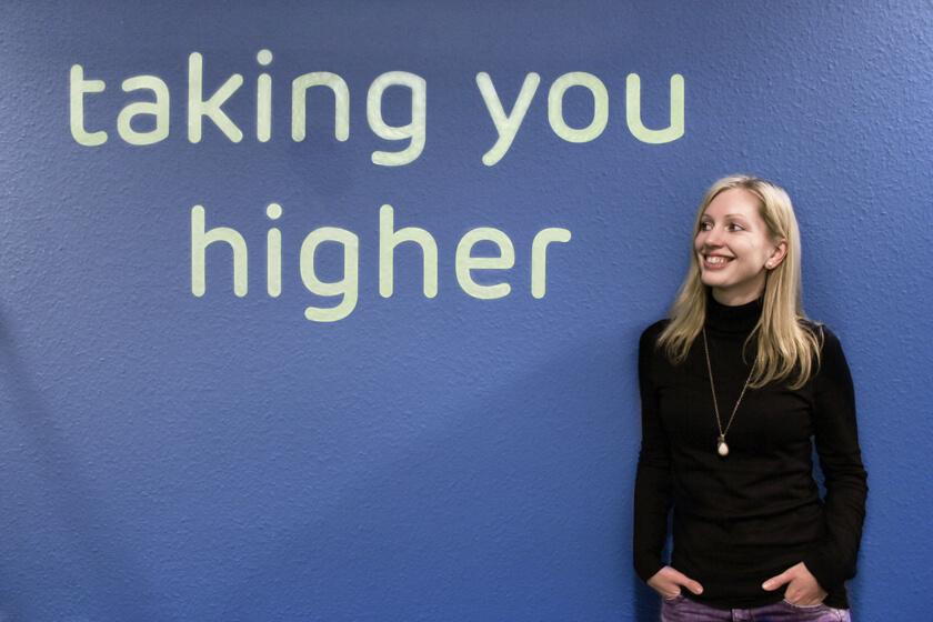 Digitale Leute - Kerstin Timm - Artaxo - Kerstin im Portrait, posiert neben einem Spruch im Flur von Ataxo in Hamburg: Taking you higher.