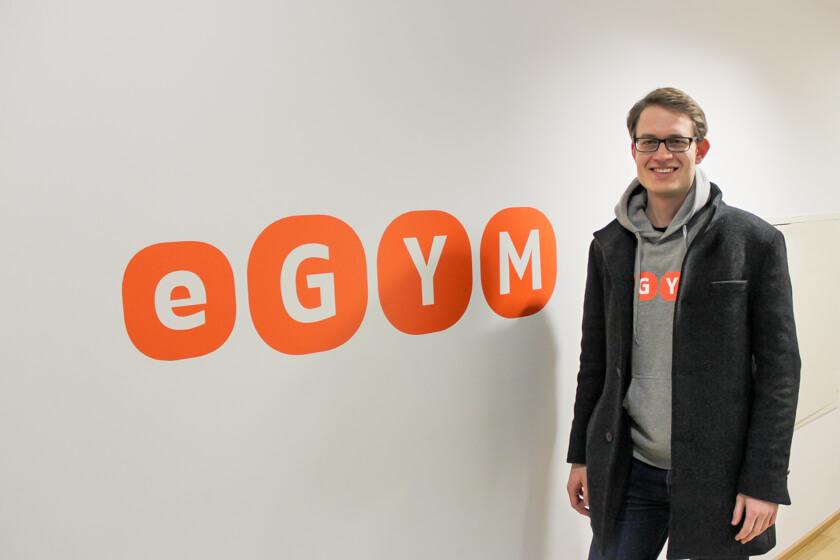 Digitale Leute - Sandro Gießl - eGym - Sandro vor dem eGym-Logo, als wir in das Büro gehen.