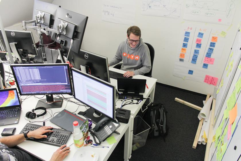 Digitale Leute - Sandro Gießl - eGym - Sandro an seinem Arbeitsplatz, umzingelt von Monitoren und Haftnotizen.