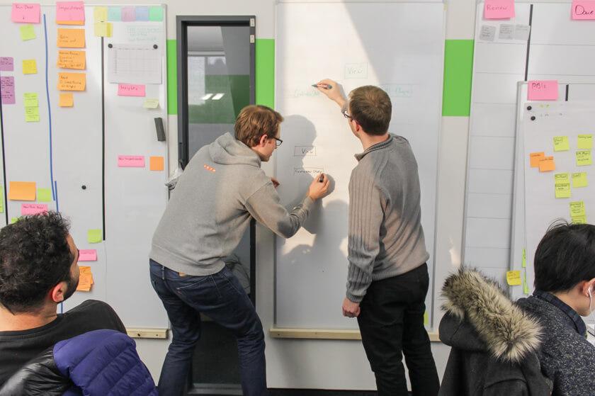 Digitale Leute - Sandro Gießl - eGym - Sandro arbeitet mit einem Kollegen auf Papier die Server-Architektur aus.
