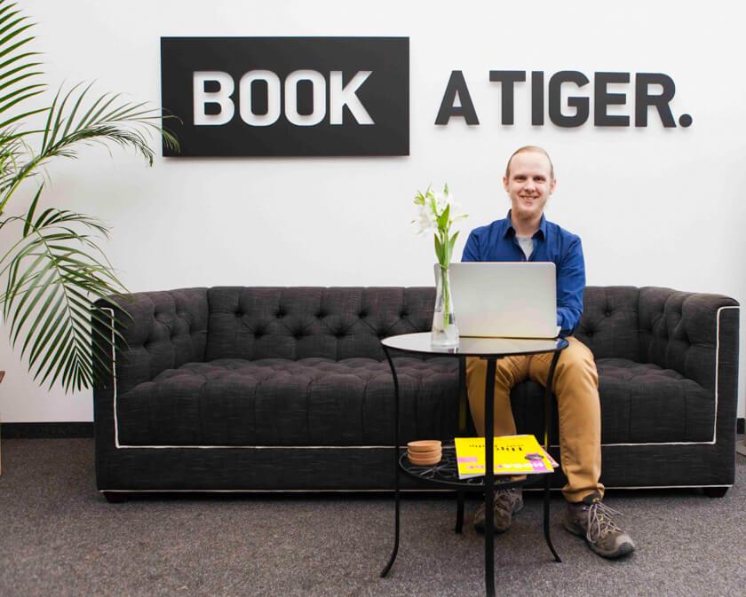 Digitale Leute - Bjarke Walling - Book A Tiger - Bjarke vor dem Book A Tiger Schiild.