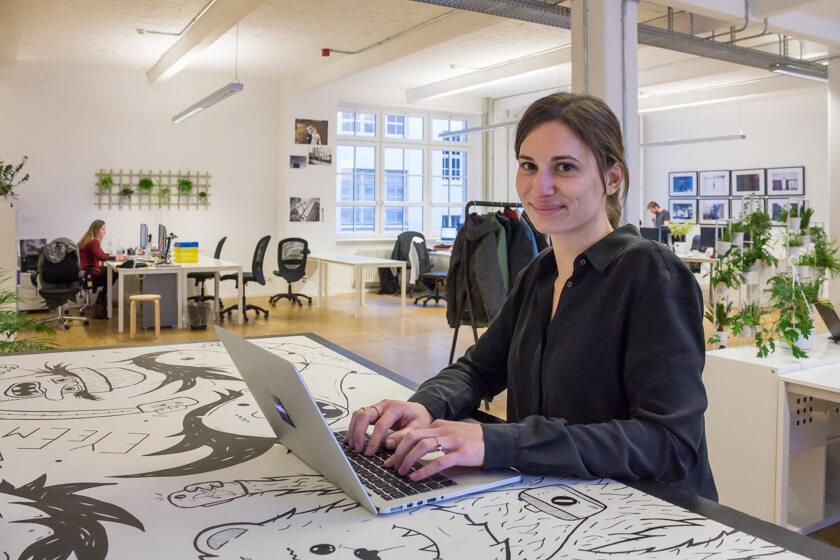 Digitale Leute - Adrienne Ossko - EyeEm - Adrienne Ossko steht an einem Konzept-Tisch im Grooßraumbüro bei EyeEm, in dem sie auch ihren Arbeitsplatz hat.