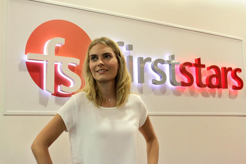 Digitale Leute - Anne Gradler - First Stars - Anna Stellt sich vor dem First Stars Logo auf.