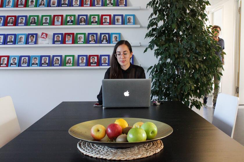 Digitale Leute - Marimar Hollenbach - Project A - Marimar sitzt vor der Wand mit all ihren Kollegen.