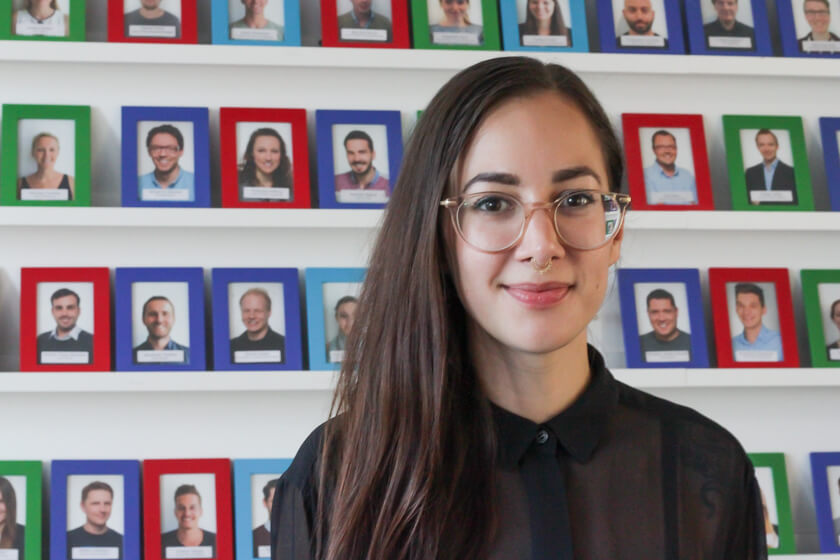 Digitale Leute - Marimar Hollenbach - Project A - Portrait von Marimar Hollenbach vor der bunten Mitarbeiterwand.