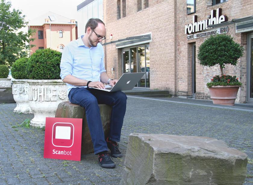 Digitale Leute - Michael Stache - Scanbot - Im Schatten des Gebäudes auf einem Steine saß ein Designer.