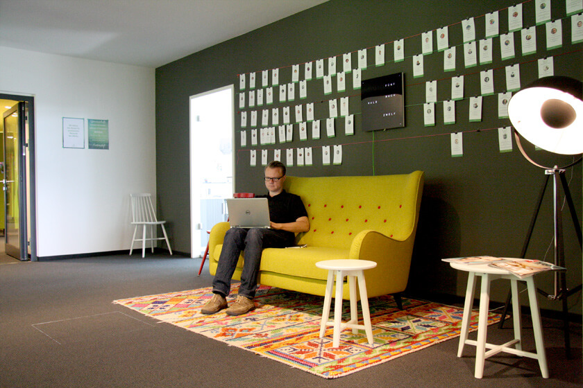 Digitale Leute - Hendrik Neumann - Chefkoch - Über der Couch hängen Bilder von Mitarbeitern