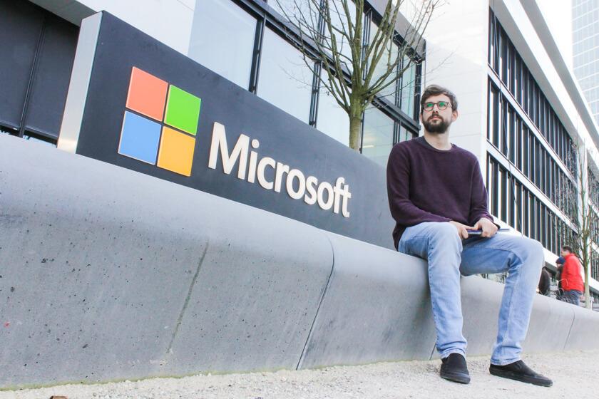 Digitale Leute - Tobias Röver - Microsoft - Tobias sitzt vor dem Microsoft Logo in München für ein Portrait.